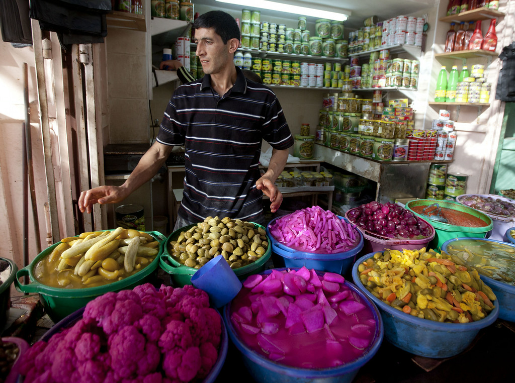 . A Palestinian vendors displays food, including pickled vegetables and olives, in preparation for Ramadan at a market in the West Bank city of Hebron, Saturday, June 28, 2014. Muslims throughout the world are preparing themselves for the holy month of Ramadan, when the observant fast from dawn till dusk. (AP Photo/Majdi Mohammed)
