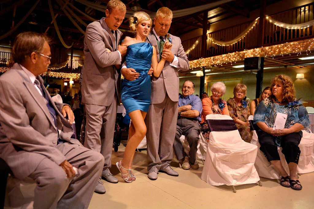 . �Brittanie didn�t want to get married until Mackenzie could walk down the aisle with her,� said the girls� father, Steve Gorden. �I didn�t know if it would ever happen or not, but it happened today.� Brother Nick Gorden, right, and best man Jeremy Buschmann aid Mackenzie�s steps. (Photo By Craig F. Walker / The Denver Post)