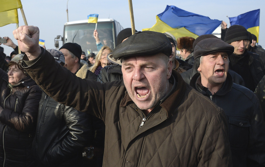 . Ukrainians carrying their country\'s flags stage a protest at the Chongar check point blocking the entrance to Crimea on March 7, 2014. Two buses carrying OSCE observers trying to enter Crimea turned back Friday after being blocked by armed men at a checkpoint, an AFP reporter said. Two sources within the mission said the team of 47 military and civilian observers was returning to the Ukrainian city of Kherson where they had spent the night after being similarly blocked on Thursday. ALEXANDER NEMENOV/AFP/Getty Images