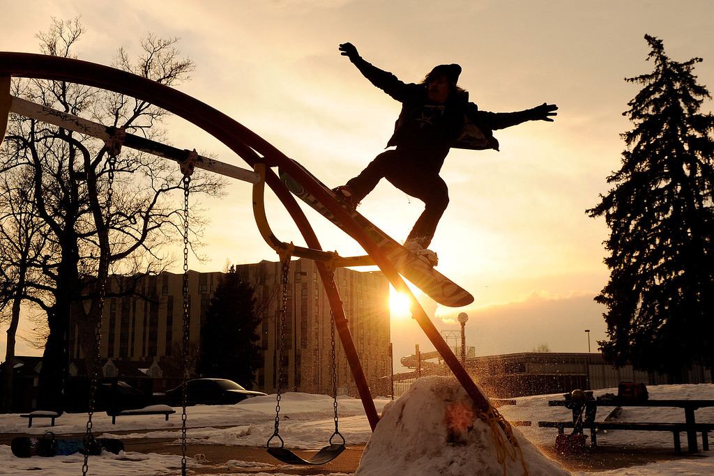 . Ketih Driessen uses the swing set as a rail while snowboarding with friends at Lincoln Park  on Sunday, February 12, 2012. AAron Ontiveroz, The Denver Post