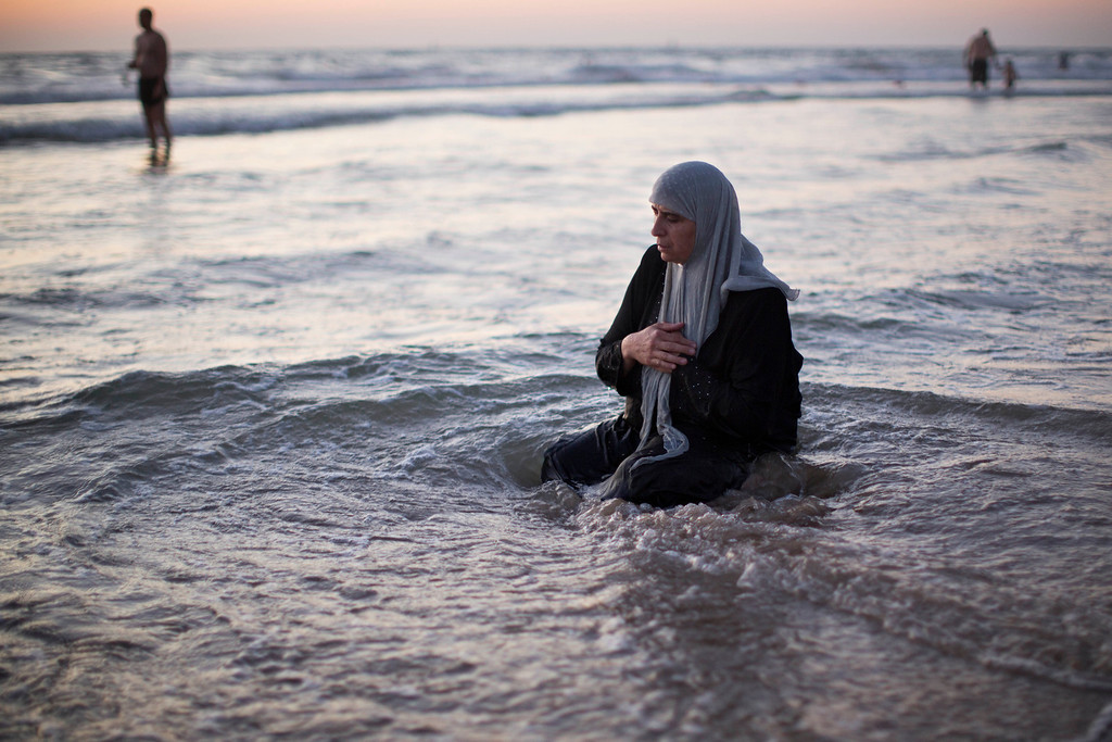 . A Palestinian woman prays in the Mediterranean sea during the first day of the Eid al-Fitr holiday in Tel Aviv, Israel, Thursday, Aug. 8, 2013. The three-day Eid al-Fitr holiday marks the end of the holy fasting month of Ramadan. One of the most important holidays in the Muslim world, Eid al-Fitr, is marked with prayers, family reunions and other festivities. (AP Photo/Oded Balilty)