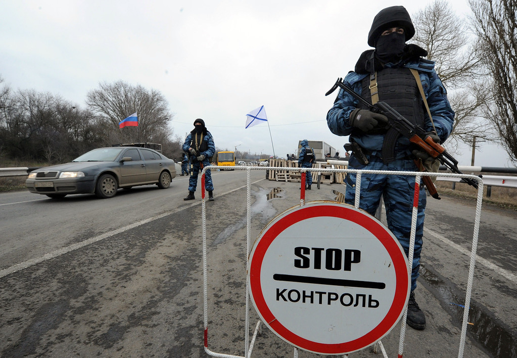 . Armed masked men who call  themselves members of Ukraine\'s disbanded elite Berkut riot police force stand at their checkpoint under a Russian national (L) and Russian naval (R) flags on a highway that connect Black Sea Crimea  peninsula to mainland Ukraine near the city of Armyansk, on February 28, 2014.  AFP PHOTO / VIKTOR DRACHEV/AFP/Getty Images