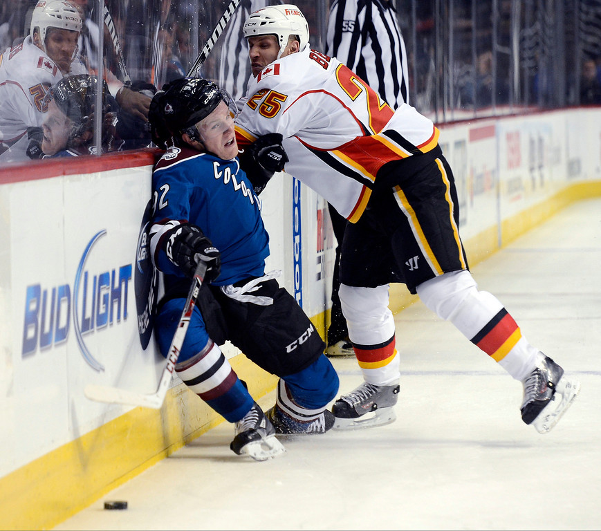 . Gabriel Landeskog (92) of the Colorado Avalanche gets pounded against the boards gets pounded against the boards by Steve Begin (25) of the Calgary Flames during the second period April 8, 2013 at Pepsi Center. (Photo By John Leyba/The Denver Post)