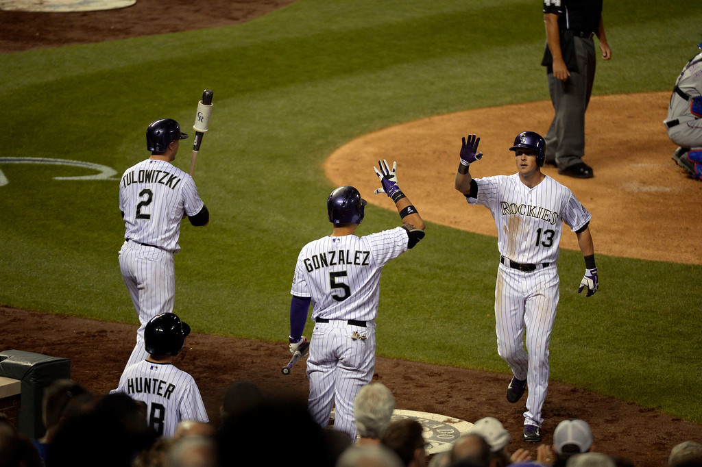 . DENVER, CO - MAY 06: Colorado Rockies center fielder Drew Stubbs (13) high fives Colorado Rockies left fielder Carlos Gonzalez (5) after his home run in the seventh inning against the Texas Rangers May 6, 2014 at Coors Field. (Photo by John Leyba/The Denver Post)
