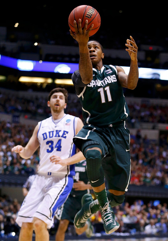 . Michigan State Spartans guard Keith Appling (11) goes to the basket to score past Duke Blue Devils forward Ryan Kelly (34) during their Midwest Regional NCAA men\'s basketball game in Indianapolis, Indiana, March 29, 2013. REUTERS/Jeff Haynes