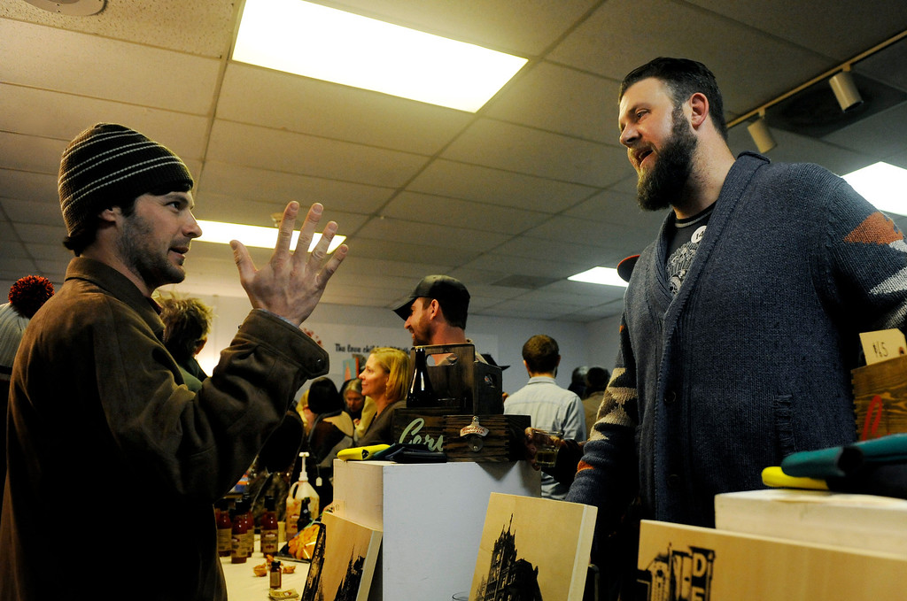 . Dave Roggeman, right, owner of IndyInk, talks with interested buyer, Adam Slutzker, left, about his work on Dec. 6 at the Holiday Mancraft 2013 craft fair at the VFW Post in Denver, Colo., where over 40 vendors showcased their goods, drank cocktails and beer, and competed in a mustache contest. Photo by Jamie Cotten, Special to The Denver Post