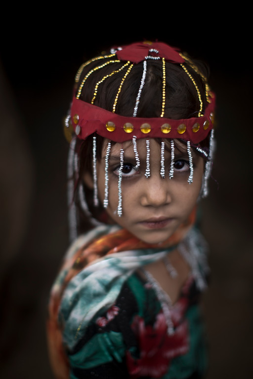 """. Sameena Hazrat, 5, a Pakistani girl who was displaced with her family from Pakistan\'s tribal areas due to fighting between the Taliban and the army, dressed in new clothes to celebrate the Muslim holiday of Eid al-Adha, or \""""Feast of Sacrifice,\"""" stands outside her home in a poor neighborhood on the outskirts of Islamabad, Pakistan, Thursday, Oct. 17, 2013. (AP Photo/Muhammed Muheisen)"""