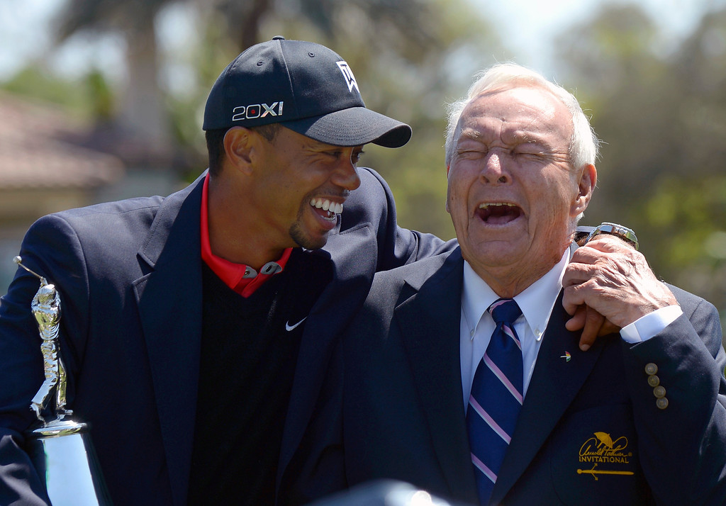 . Tiger Woods, left, and Arnold Palmer share a laugh during the trophy presentation after Woods won the Arnold Palmer Invitational golf tournament in Orlando, Fla., Monday, March 25, 2013. (AP Photo/Phelan M. Ebenhack)