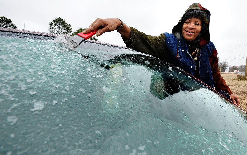 . Freezing rain falls as Darlene Crum scrapes ice from her car windshield as she prepares to drive home from her job at Resurrection School in Montgomery, Ala. on Tuesday Jan. 28, 2014.  (AP Photo/The Montgomery Advertiser, Mickey Welsh)