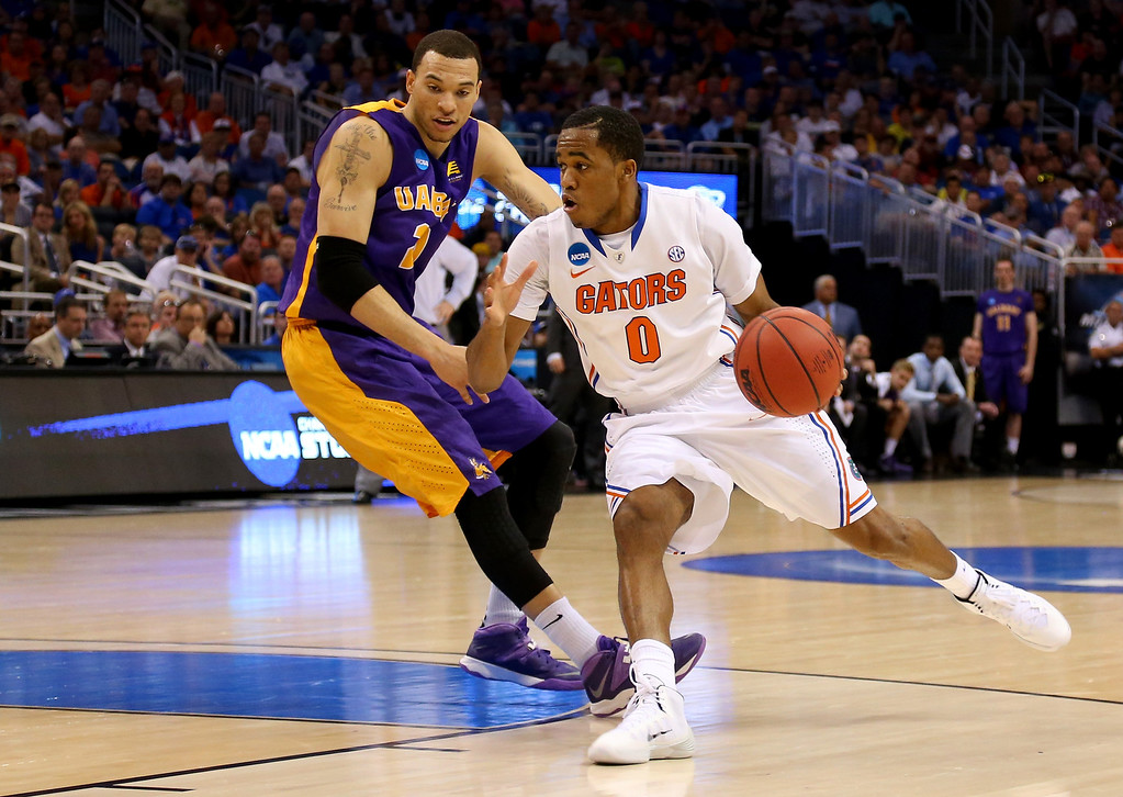 . ORLANDO, FL - MARCH 20:  Kasey Hill #0 of the Florida Gators drives on Gary Johnson #20 of the Albany Great Danes in the second half during the second round of the 2014 NCAA Men\'s Basketball Tournament at Amway Center on March 20, 2014 in Orlando, Florida.  (Photo by Mike Ehrmann/Getty Images)