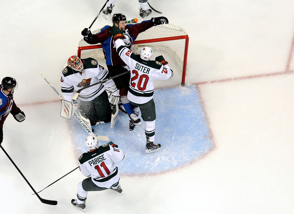 . Ryan Suter (20) of the Minnesota Wild shoves Gabriel Landeskog (92) of the Colorado Avalanche into the net in the Minnesota zone during the first period of action. The Colorado Avalanche hosted the Minnesota Wild in the first round of the Stanley Cup Playoffs at the Pepsi Center in Denver, Colorado on Saturday, April 19, 2014. (Photo by John Leyba/The Denver Post)