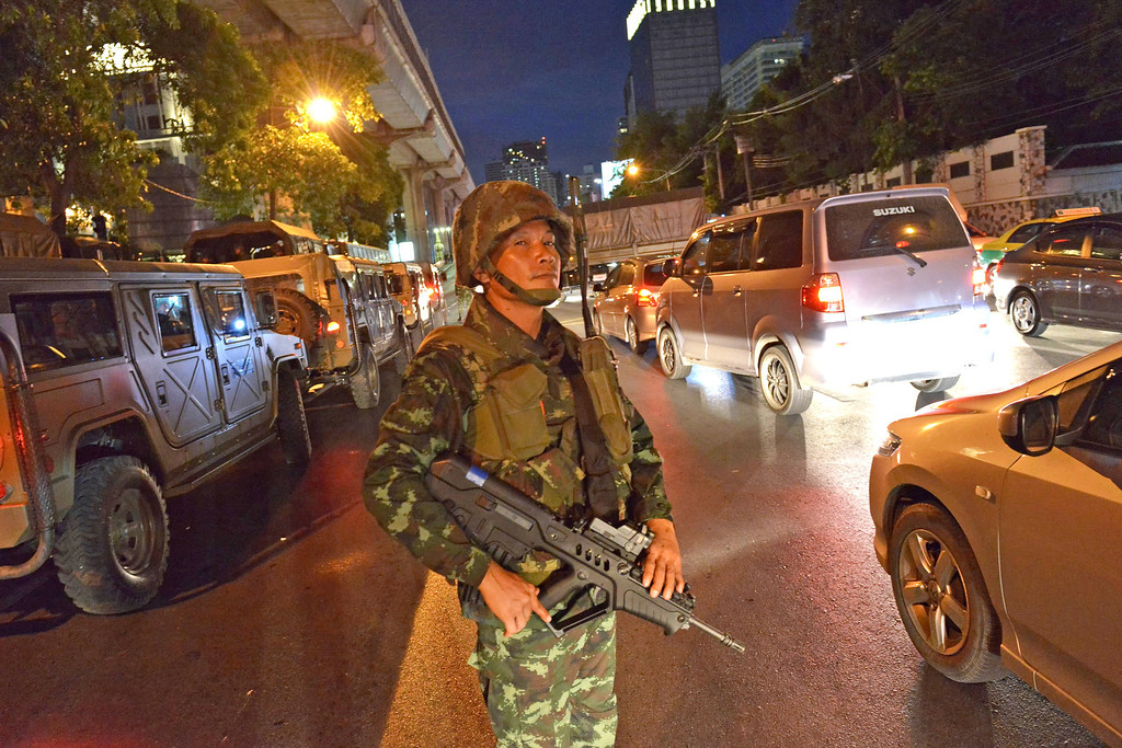 . A Thai army soldier looks on as rush hour traffic moves slowly along a city centre road after protesters hold an anti-coup rally on May 23, 2014 in Bangkok, Thailand. Anti-coup protesters rallied in Bangkok\'s shopping district, a day after the military seized control in a bloodless coup. Martial law imposes a 10pm to 5am curfew and public assembly is banned. (Photo by Rufus Cox/Getty Images)