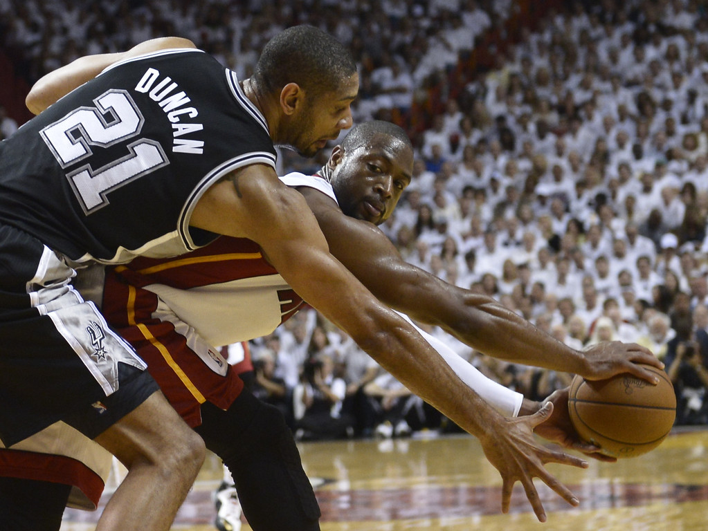 . Dwyane Wade (R) of the Miami Heat vies with Tim Duncan of the San Antonio Spurs during the third quarter of Game 7 of the NBA Finals at the American Airlines Arena June 20, 2013 in Miami, Florida. The Miami Heat won 95-88 to win the championship.  BRENDAN SMIALOWSKI/AFP/Getty Images