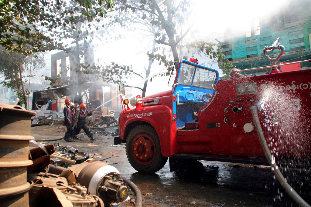 . In this Thursday, March, 21, 2013 photo, Myanmar fire fighters put out fires in a burning building following ethnic unrest between Buddhists and Muslims in Meikhtila, Mandalay division, about 550 kilometers (340 miles) north of Yangon, Myanmar. Burning fires from two days of Buddhist-Muslim violence that killed at least 20 people smoldered across a central Myanmar town Friday as residents cowered indoors amid growing fears the country\'s latest bout of sectarian bloodshed could spread. The government\'s struggle to contain the unrest in Meikhtila is proving another major challenge President Thein Sein\'s reformist administration as it attempts to chart a path to democracy after nearly half a century of military rule that once crushed all dissent. (AP Photo)