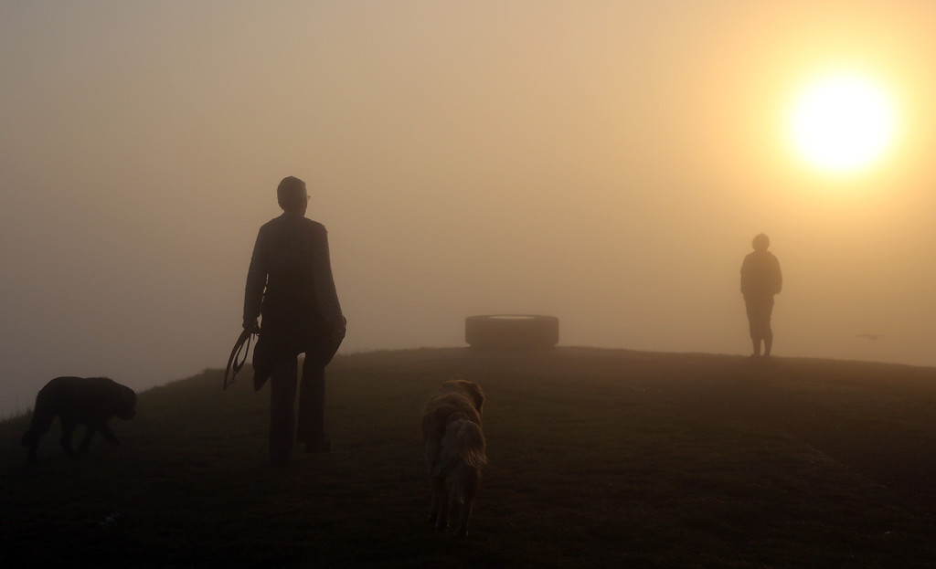 . Dog walkers walk to the top of Glastonbury Tor as the rising sun begins to clear the early morning mist and fog near the town of Glastonbury on September 4, 2013 in Somerset, England.  (Photo by Matt Cardy/Getty Images)