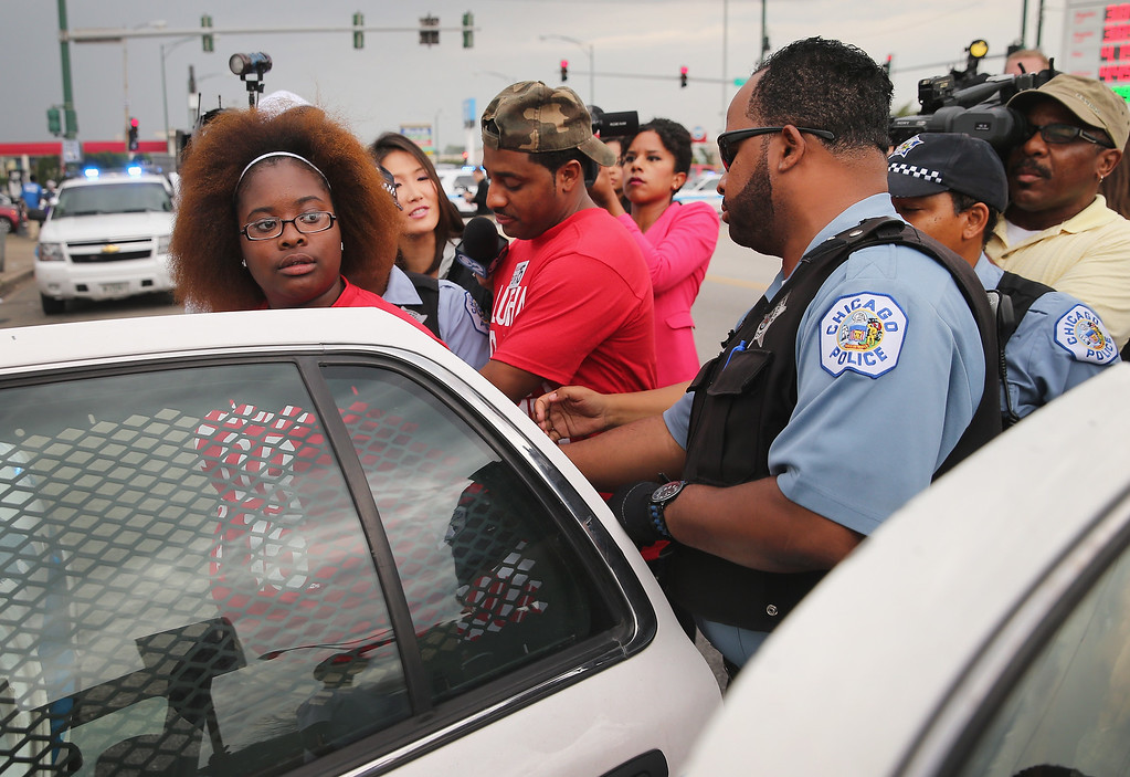 . CHICAGO, IL - SEPTEMBER 04:  Police arrest demonstrators who were protesting for an increase in wages for fast food workers and home care workers after they staged a sit-in on 87th Street during the morning rush hour on September 4, 2014 in Chicago, Illinois. Nineteen protestors were arrested at the demonstration. The demonstration was one of many staged nationwide in a push to increase wages to $15-per-hour for the workers.  (Photo by Scott Olson/Getty Images)