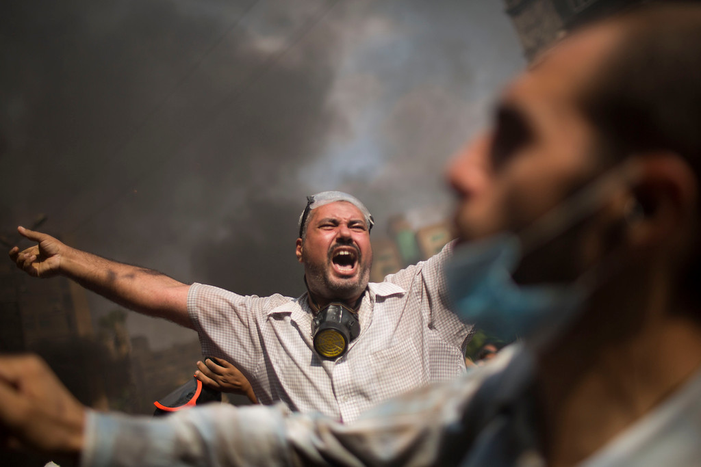 . Supporters of ousted Islamist President Mohammed Morsi shout during clashes with Egyptian police at the Rabaah Al-Adawiya protest camp in Cairo\'s Nasr City district, Egypt, Wednesday, Aug. 14, 2013.  (AP Photo/Manu Brabo)