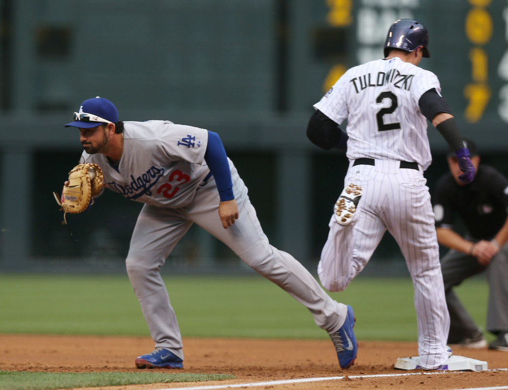 . Los Angeles Dodgers first baseman Adrian Gonzalez, left, fields the throw to put out Colorado Rockies\' Troy Tulowitzki at first base to end the first inning of a baseball game in Denver on Thursday, July 3, 2014. (AP Photo/David Zalubowski)