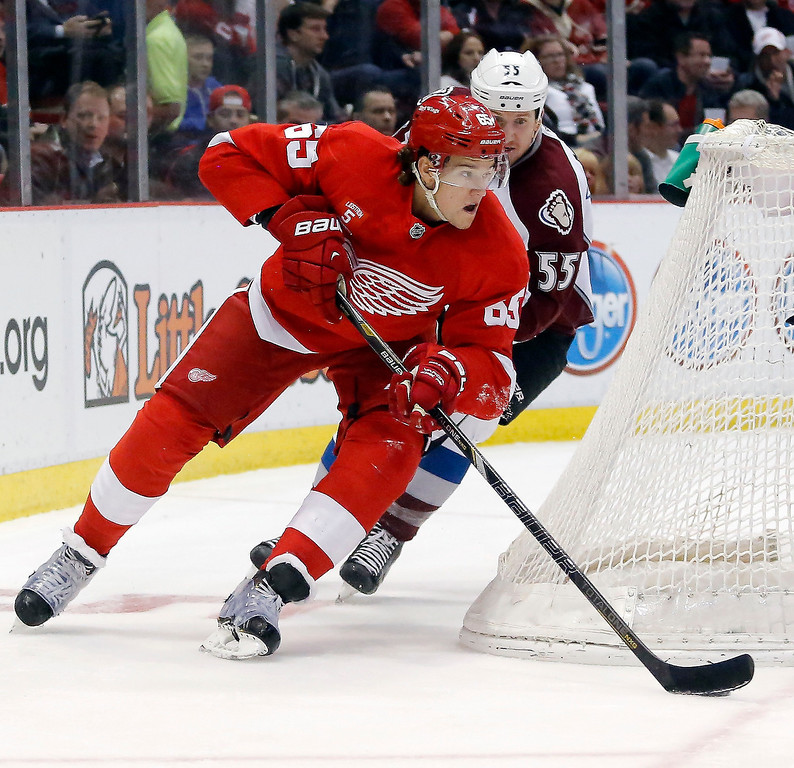 . Detroit Red Wings\' Danny DeKeyser (65) takes the puck from behind the net against Colorado Avalanche\'s Cody McLeod during the first period of an NHL hockey game Thursday, March 6, 2014, in Detroit. (AP Photo/Duane Burleson)