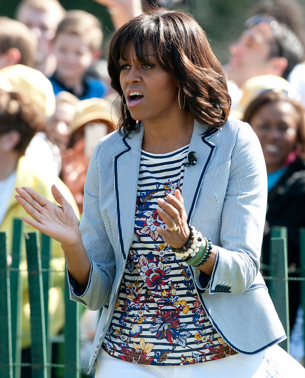 . First Lady Michelle Obama cheers during the White House Easter Egg Roll on the South Lawn of the White House in Washington, DC, April 1, 2013. Obama hosts the annual event, featuring live music, sports courts, cooking stations, storytelling and Easter egg rolling. AFP PHOTO / Saul LOEB/AFP/Getty Images