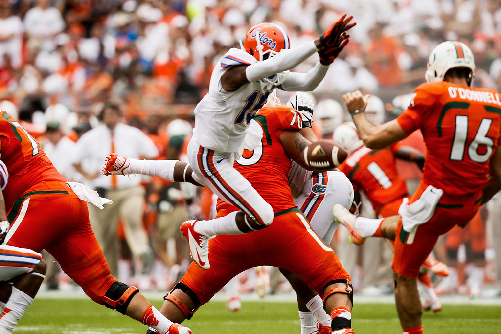 . Florida defensive back Loucheiz Purifoy (15) blocks a punt by Miami punter Pat O\'Donnell (16) during the first half of an NCAA college football game in Miami Gardens, Fla., Saturday, Sept. 7, 2013. Miami defeated Florida 21-16.  (AP Photo/The Tampa Bay Times, Will Vragovic)