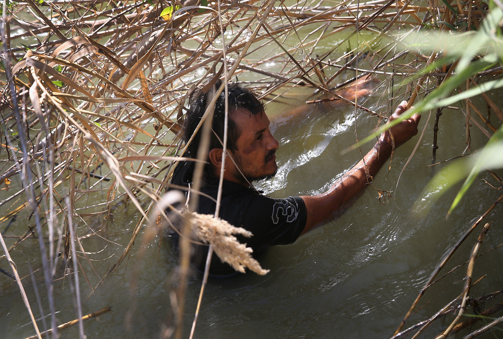 . MISSION, TX - APRIL 11:  A suspected narco trafficker stands caught in the weeds on the bank of the Rio Grande River at the U.S.-Mexico Border on April 11, 2013 in Mission, Texas. U.S. Border Patrol agents with helicopter support from the U.S. Office of Air and Marine broke up a marijuana smuggling operation from Mexico into Texas. The man in the river freed himself and swam back across the river into Mexico. In addition to heavy drug smuggling in the area, U.S. Border Patrol agents say they have also seen an additional surge in immigrant traffic in Texas\' Rio Grande Valley sector since immigration reform negotiations began this year in Washington D.C.  (Photo by John Moore/Getty Images)