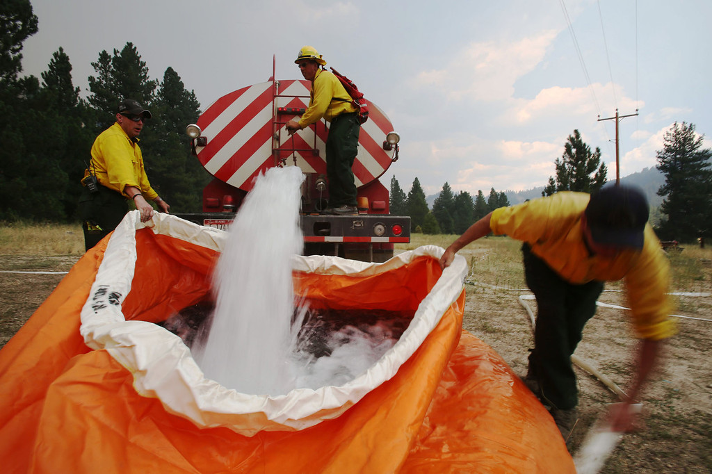 . Members of the Mountain Home Fire Department fill a water reservoir called a pumpkin, with 1,800 gallons of water on Monday, Aug. 12, 2013,  as they prepare to defend homes from the more than 80,000-acre Elk Complex Fire burning near Pine, Idaho.   (AP Photo/Times-News, Ashley Smith)