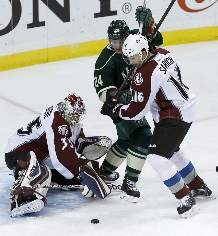 . Colorado Avalanche defenseman Cory Sarich (16) holds Minnesota Wild left wing Matt Cooke (24) off the puck as Avalanche goalie Jean-Sebastien Giguere (35) covers the net during the third period of an NHL hockey game in St. Paul, Minn., Friday, Nov. 29, 2013. The Avalanche won 3-1. (AP Photo/Ann Heisenfelt)