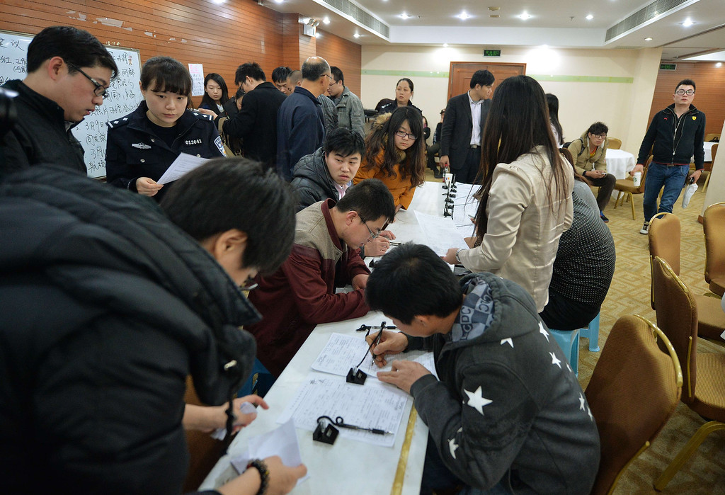 . Relatives of victims from the missing Malaysia Airlines Boeing 777-200 plane complete paperwork for their Chinese passports to be ready to travel to the crash site, in Beijing on March 9, 2014.  Malaysia said a missing airliner carrying 239 people may have inexplicably turned back as authorities launched a terror probe into the plane\'s sudden disappearance, investigating suspect passengers who boarded with stolen passports.           MARK RALSTON/AFP/Getty Images