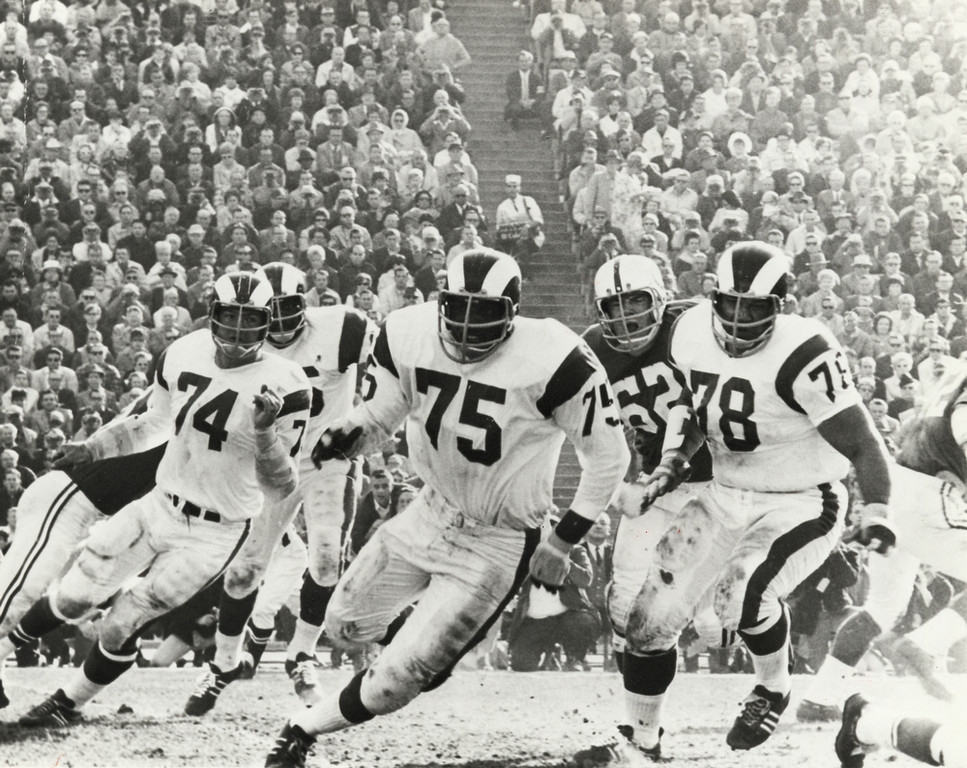 """. In this Dec. 17, 1967 photo provided by NFL Photos, Los Angeles Rams defensive David \""""Deacon\"""" Jones (75) and defensive tackles Merlin Olsen (74) and Roger Brown (78) battle the Baltimore Colts in Los Angeles.  (AP Photo/NFL Photos)"""