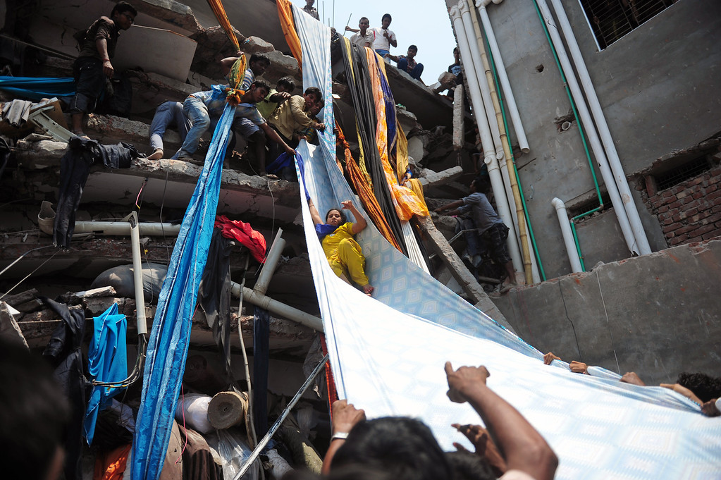 . Bangladeshi garment workers help evacuate a survivor using lengths of textile as a slide to evacuate from the rubble after an eight-story building collapsed in Savar, on the outskirts of Dhaka, on April 24, 2013.  AFP PHOTO/Munir uz ZAMAN/AFP/Getty Images