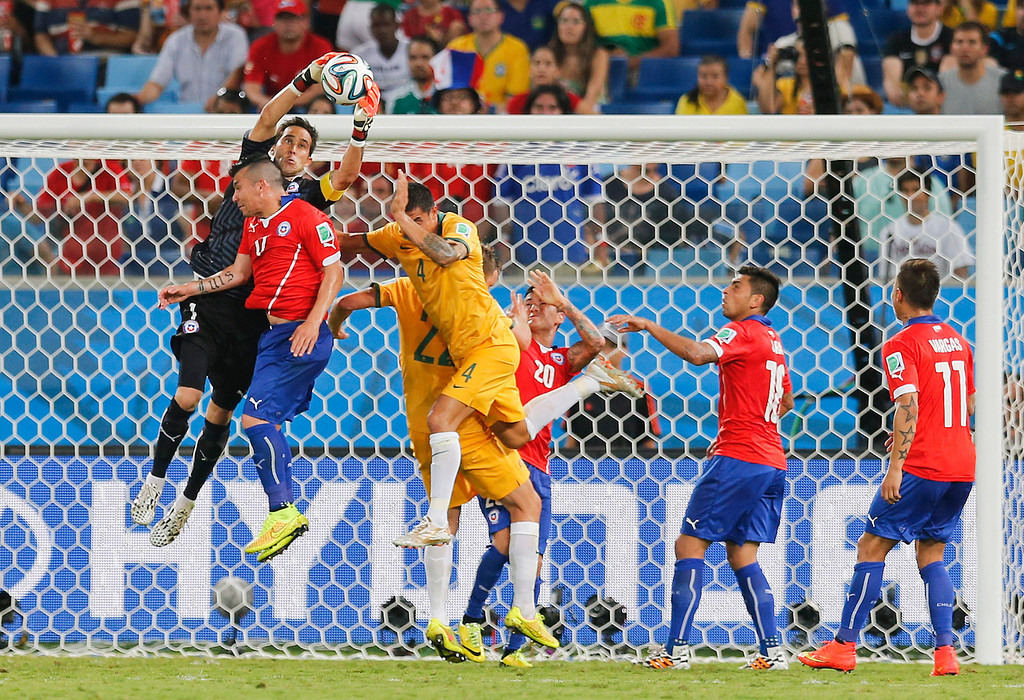 . Chile\'s goalkeeper Claudio Bravo, leaps into the air to claim a cross during the group B World Cup soccer match between Chile and Australia in the Arena Pantanal in Cuiaba, Brazil, Friday, June 13, 2014.  (AP Photo/Frank Augstein)