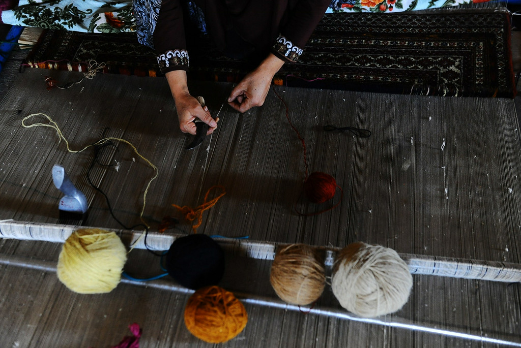 . In this picture taken on June 26, 2014, an Afghan worker weaves a carpet at a traditional factory in Herat.  AFP PHOTO/Aref Karimi/AFP/Getty Images