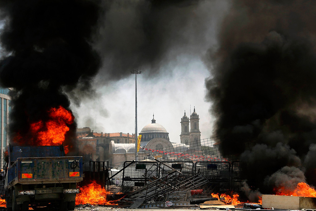 . The Greek Orthodox Church of Hagia Triada is framed by a burning barricade during clashes in Istanbul\'s Taksim square June 11, 2013.  REUTERS/Yannis Behrakis
