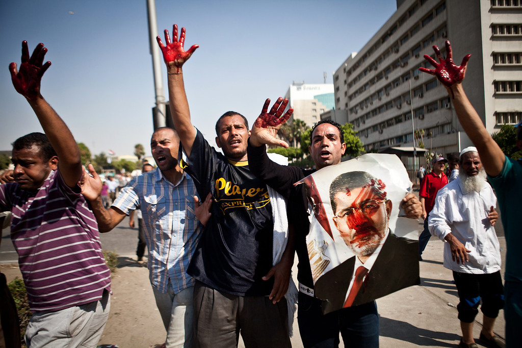 ". Islamist protesters, one holding a picture of ousted president Mohammed Morsi, hold up blood-stained hands after troops opened fire on a protest in front of the Republican Guard headquarters in Nasr City, Cairo, Egypt, Friday, July 5, 2013. Army troops opened fire Friday on protesters demanding the reinstatement of toppled President Mohammed Morsi, killing at least one, as supporters of the Islamist leader rallied across Egypt chanting ""Down with military rule!\"" (AP Photo/Virginie Nguyen Hoang)"