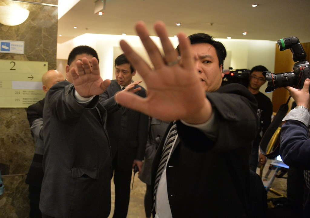""". Chinese plainclothes security block photos of a man trying to hand out leaflets to journalists with his theory about the missing Malaysia Airlines flight MH370 at a hotel in Beijing on March 21, 2014. After two weeks of false leads, Australia revived the investigation on the mysterious disappearance of flight MH370 when it announced the detection of two \""""objects\"""" in the southern Indian Ocean, some 2,500 kilometers (1,553 miles) southwest of Perth in Western Australia.           AFP PHOTO/Mark RALSTON/AFP/Getty Images"""