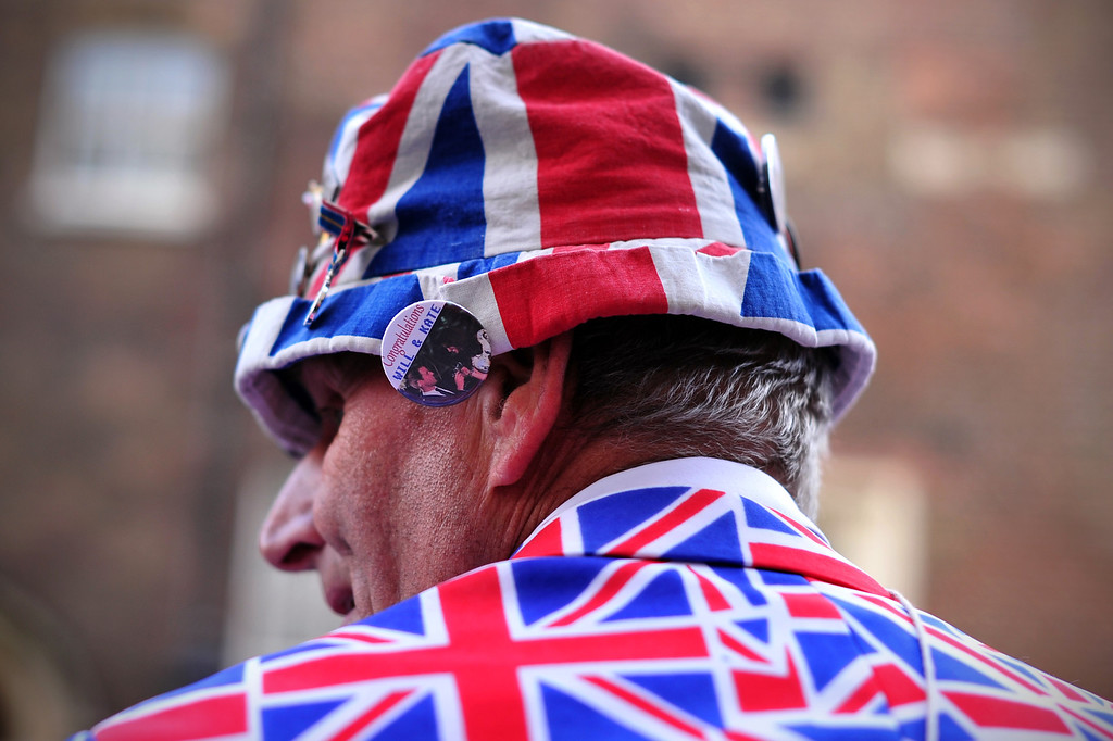 ". A royal supporter wears a ""Will and Kate\"" pin on his Union Flag hat as he waits opposite St James\'s Palace in central London on October 23, 2013, where Prince George of Cambridge will be baptized later in the day inside Chapel Royal. AFP PHOTO/CARL COURT/AFP/Getty Images"