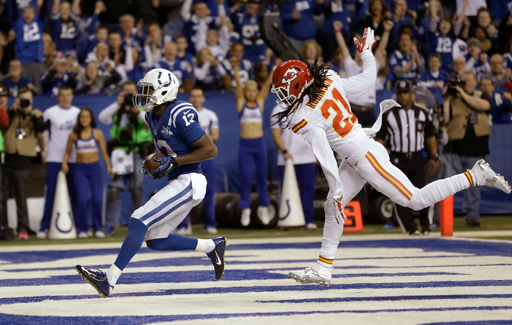 . Indianapolis Colts wide receiver T.Y. Hilton (13) scores as Kansas City Chiefs cornerback Dunta Robinson (21) defends during the first half of an NFL wild-card playoff football game Saturday, Jan. 4, 2014, in Indianapolis. (AP Photo/Michael Conroy)