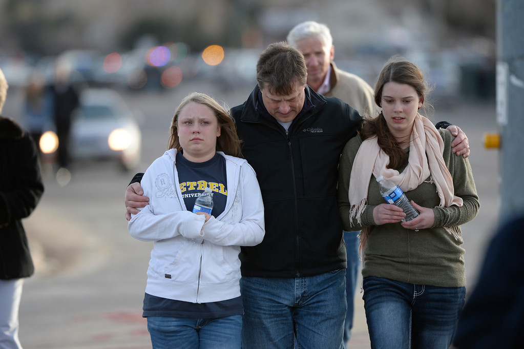 ". CENTENNIAL, CO. - DECEMBER 13: Todd Skodda walks with his daughters, Emily, 18, left and Abby, 16,at Arapahoe High School in Centennial, CO December 13, 2013. A student who carried a shotgun into Arapahoe High School and asked where to find a specific teacher opened fire on Friday, wounding two fellow students before apparently killing himself, Arapahoe County Sheriff Grayson Robinson said. Abby said she hid in her in Chemistry class when the shooting stated, ""all we did was pray, \'God deliver us,\' and he did.\"" (Photo By Craig F. Walker / The Denver Post)"