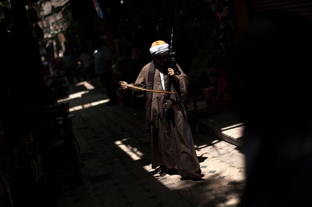 . A street musician plays while walking through an alley in the Khan El-Khalili market, a popular destination for tourists, in Cairo, Egypt, Wednesday, Aug. 21, 2013. Riots and killings that erupted across the country after the crackdown against followers of ousted President Mohammed Morsi have delivered a severe blow to Egypt\'s tourism industry, which until recently accounted for more than 11 percent of the country\'s gross domestic product and nearly 20 percent of its foreign currency revenues. (AP Photo/Manu Brabo)