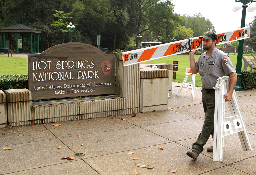 . Hot Springs National Park employee Stacy Jackson carries a barricade while closing Arlington Lawn in Hot Springs National Park Tuesday, Oct. 1, 2013, because of the federal government\'s partial shutdown. (AP Photo/The Sentinel-Record, Richard Rasmussen)