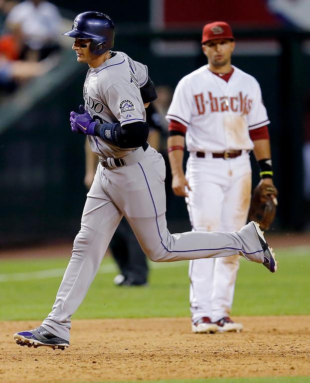 . Colorado Rockies\' Troy Tulowitzki, left, rounds the bases after hitting a solo home run as Arizona Diamondbacks\' Martin Prado looks on during the sixth inning of a baseball game on Monday, April 28, 2014, in Phoenix. (AP Photo/Matt York)