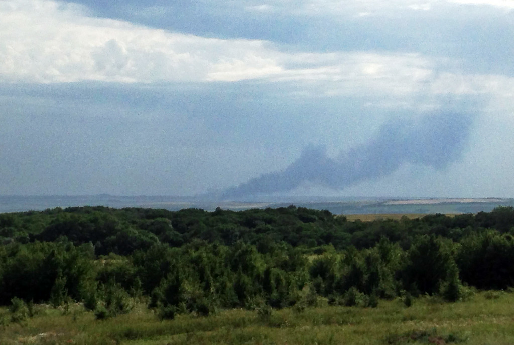 . In this photo taken with a mobile phone provided by Andrei Kashtanov, smoke rises from where a Malaysia Airlines commercial plane crashed in eastern Ukraine, Thursday, July 17, 2014. Malaysia Airlines has said 295 people were aboard the flight from Amsterdam to Kuala Lumpur. (AP Photo/Andrei Kashtanov)