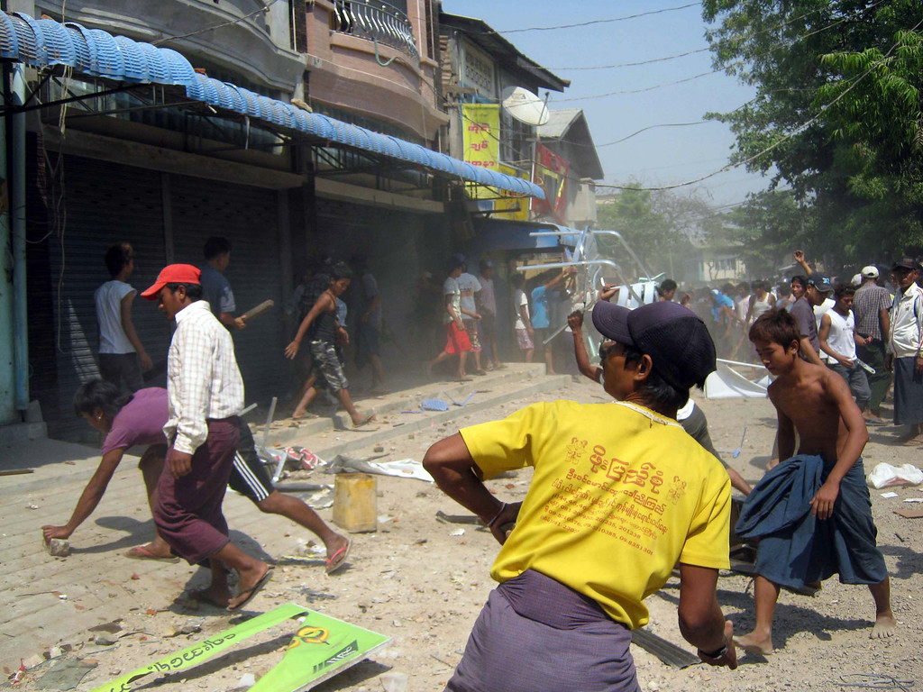 . In this Thursday, March. 21, 2013 photo, a group of people try to destroy a building in Meikhtila, where Ethnic unrest between Buddhists and Muslims continues, in Mandalay division, about 550 kilometers (340 miles) north of Yangon, Myanmar, Friday, March.22, 2013. (AP Photo)