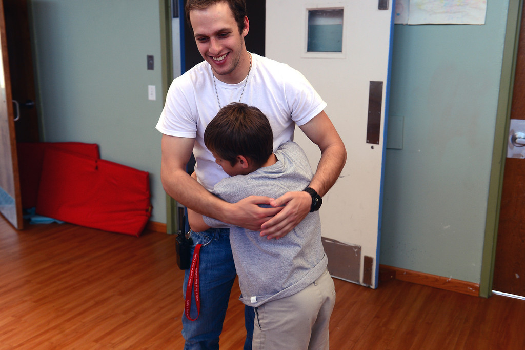. Mental health worker  Thomas Haft gets a hug one of the children after school in the residential cottages on campus at  Mount Saint Vincent Home in in Denver,  Co on March 19, 2014.  (Photo By Helen H. Richardson/ The Denver Post)