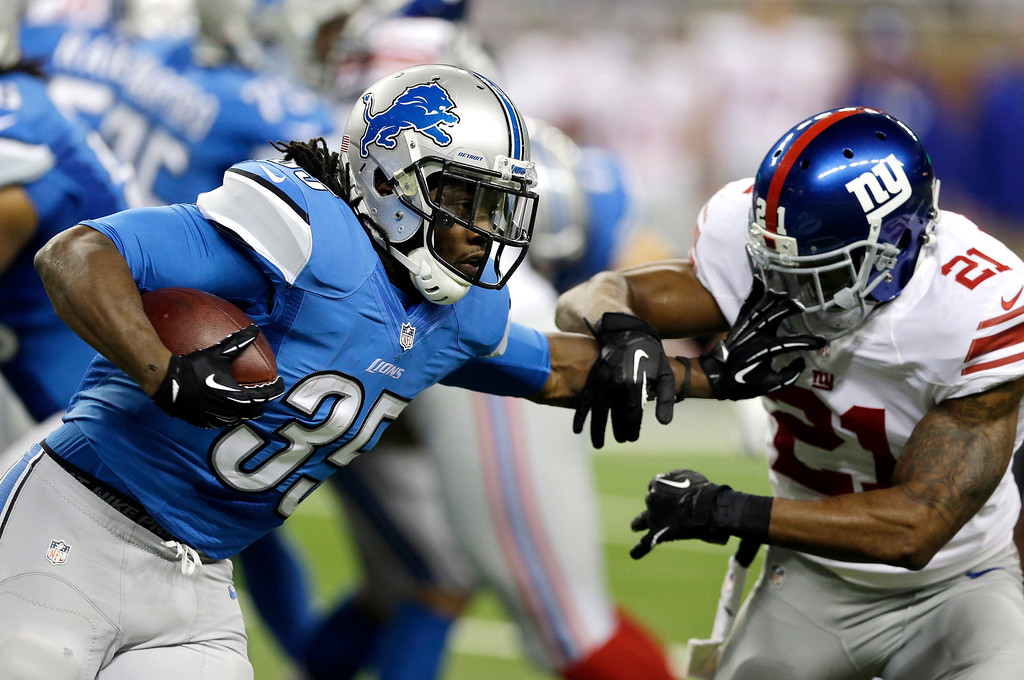 . Detroit Lions running back Joique Bell (35) pushes New York Giants free safety Ryan Mundy (21) during the first quarter of an NFL football game, Sunday, Dec. 22, 2013, in Detroit. (AP Photo/Carlos Osorio)