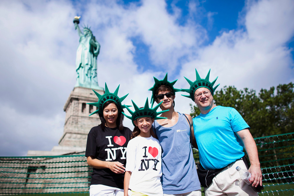 . (R-L) Rick, Connor, Claire and Lalita Perkins pose for a picture as they visit the Statue of Liberty and Liberty Island during its reopening to the public in New York, July 4, 2013. Under steamy summer skies, tourists in New York flocked to ferries headed for the Statue of Liberty, re-opening with an Independence Day ceremony after closing in October as Superstorm Sandy approached.  REUTERS/Eduardo Munoz