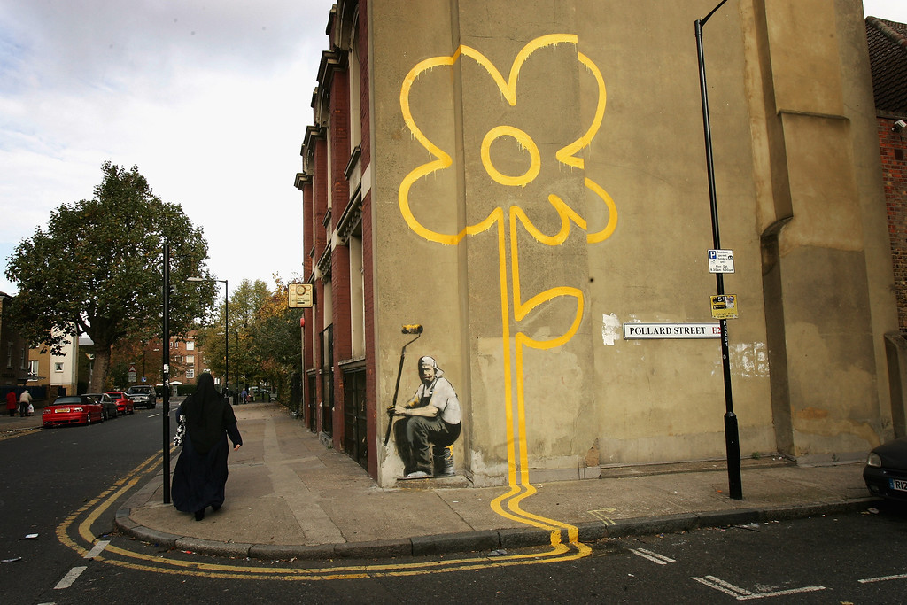 . LONDON - NOVEMBER 01: A woman walks past a new example of \'art\' by self styled guerilla artist Banksy on Pollard Street on November 1, 2007 in London, England.  Recent works of art by Banksy have been bought for hundreds of thousands of pounds by celebrities such as Brad Pitt and Angelina Jolie, however Tower Hamlets Council recently said that they had a duty to remove all graffiti in the area including anything done by Banksy. The public in Bristol recently voted over 90 percent in favour of keeping a piece of graffiti art by Banksy as it was deemed so popular.  (Photo by Chris Jackson/Getty Images)