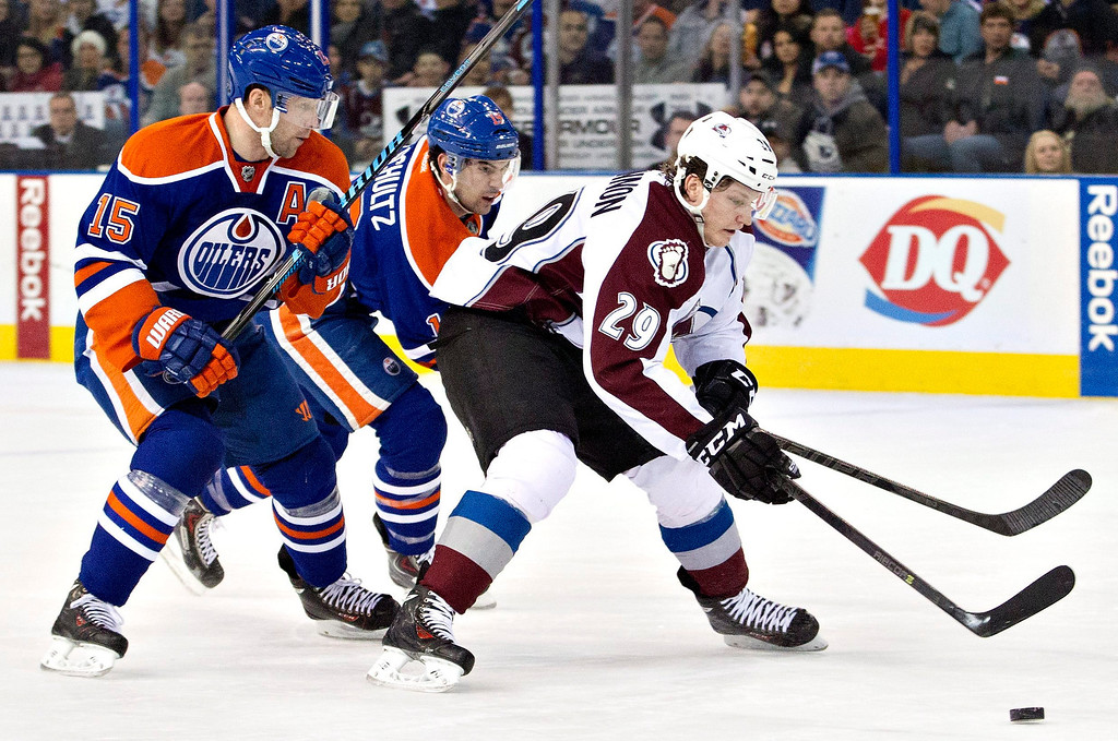 . Colorado Avalanche\'s Nathan MacKinnon (29) is chased by Edmonton Oilers\' Nick Schultz (15) and Justin Schultz (19) during first-period NHL hockey game action in Edmonton, Alberta, Thursday, Dec. 5, 2013. (AP Photo/The Canadian Press, Jason Franson)