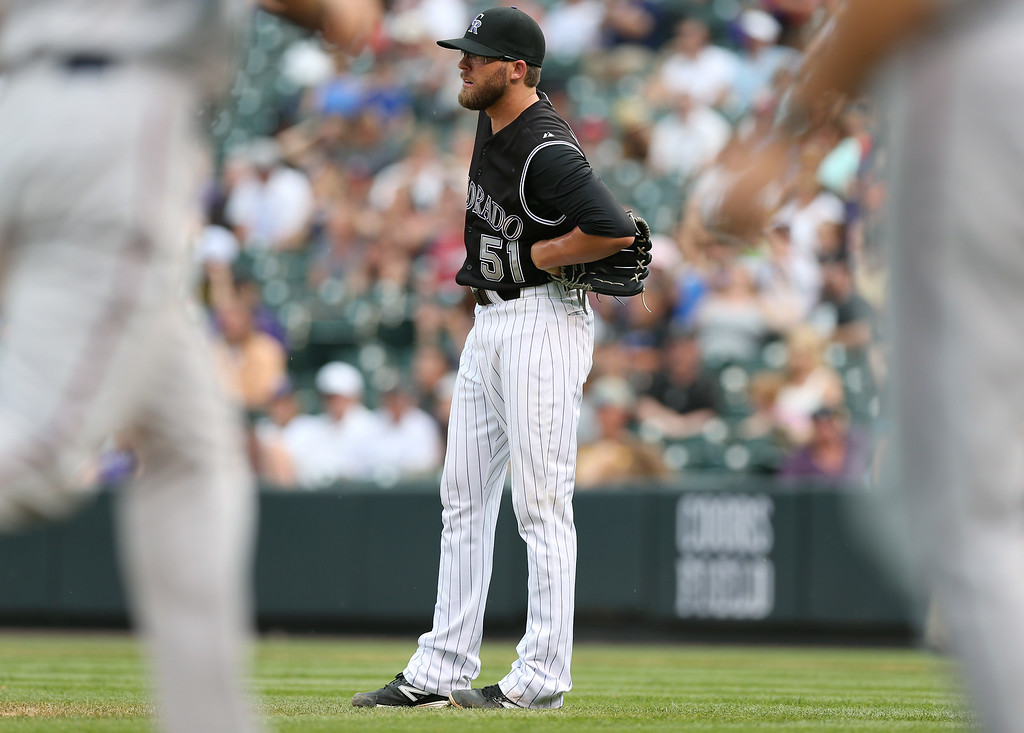 . Colorado Rockies relief pitcher Brooks Brown follows the flight of a three-run home run that he gave up to Minnesota Twins\' Brian Dozier in the ninth inning of the Twins\' 13-5 victory in an interleague baseball game in Denver on Sunday, July 13, 2014. (AP Photo/David Zalubowski)